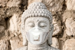 Medical mask, protection against coronavirus and other viruses. White stone statue of a Buddha in the background of masonry. Head, close-up