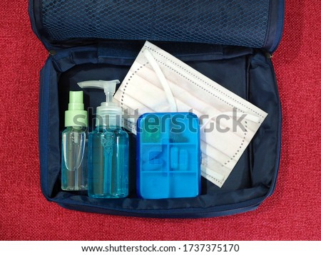 Medical mask, small bottle of alcohol gel (sanitizer) and medicine box are in the bag on red background, neccessary things during Coronavirus Pandemic.  Zdjęcia stock ©