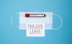 medical mask with the words paid sick leave on a blue background. concept of insurance payments to victims of the pandemic