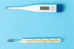 Medical mercury or electronic thermometer. The principle of old and new. Outdated and modern thermometer on blue background. Flat lay with a free space for text. Body temperature measuring device