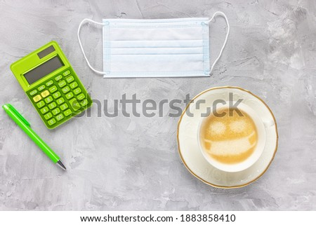 Medical mouth mask, calculator, pen, cup of coffee on gray background. Cafeteria restrictions, quarantine during coronavirus Covid-19 and tax return time concept. Flat lay, copy space Stock photo ©