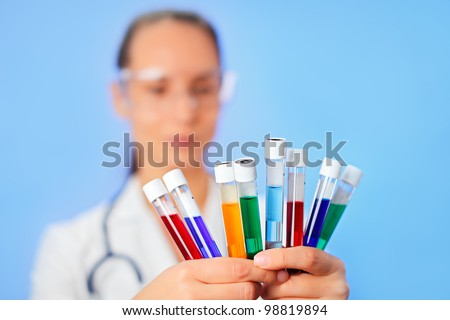 Medical multicolor test tubes with fluid sample in doctor hands closeup