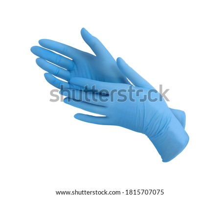 Medical nitrile gloves.Two blue surgical gloves isolated on white background with hands. Rubber glove manufacturing, human hand is wearing a latex glove. Doctor or nurse putting on protective gloves