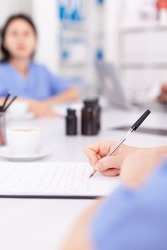 Medical nurse writing on clipboard during healthcare seminar in hospital meeting office about technology. Clinic expert therapist talking with colleagues about disease, medicine professional.