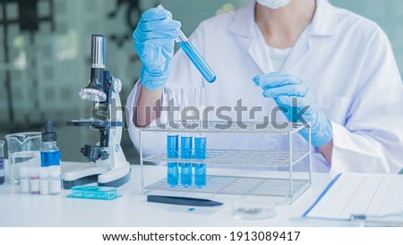 Medical or scientific researcher or man doctor looking at a test tube of clear solution in a laboratory Foto stock ©