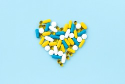 Medical pills in heart shape on blue background