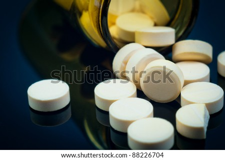 Medical pills out of their bottle on black background