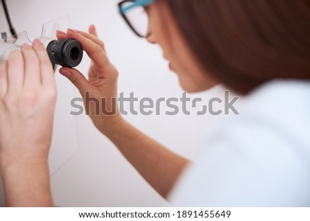 Medical practitioner gently turning the oculars of a slit lamp while tuning their accuracy Stok fotoğraf ©