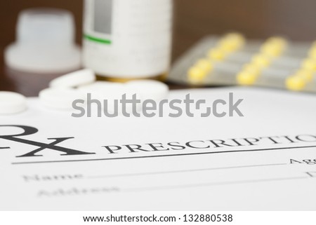 Medical prescription and pills on table