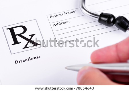 Medical prescription with a stethoscope on top of it and a doctor about to write on it - stock photo