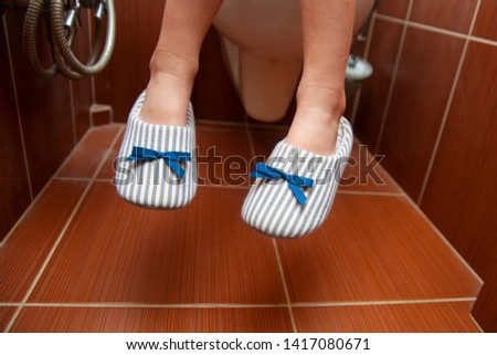 Medical problems, digestion problems (constipation, diarrhea). Child legs on the toilet. Feet in slippers with ribbon.
