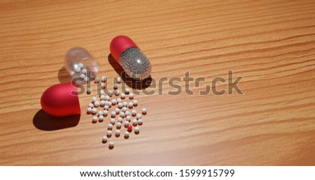 Medical product with softgel capsules (one capsule open) isolated on a wood texture table background with copy space. 3D illustration