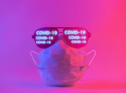 Medical protective disposable mask and glasses with inscription COVID-19 in neon pink light. Creative modern concept.