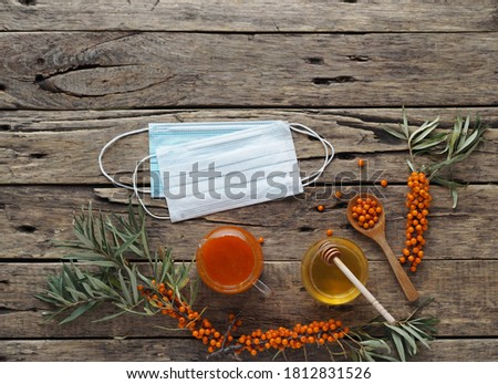 Medical protective mask with sea buckthorn branches, with berries, tea, honey and jam on a wooden background. The idea of protecting against the flu with folk natural remedies.n. Foto stock ©