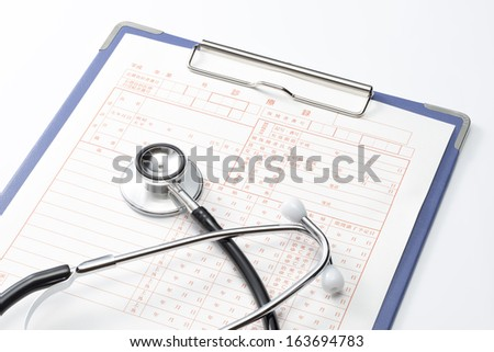 Medical record and Stethoscope on white background