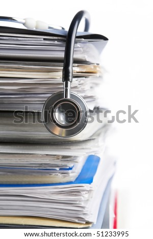 Medical record concept with stethoscope over pile of document. Selective focus on the front side of the stethoscope