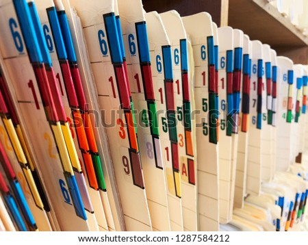 Medical records of patients in numbered and color coded folders are organized and arranged numerically and sequentially in open shelves of a clinic. #1287584212