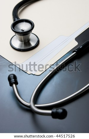 Medical Records with X Ray and Stethoscope. Focus on stethoscope bell.