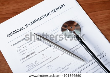 Medical report blank form with pen and stethoscope on table.