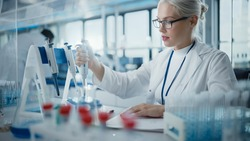 Medical Research Laboratory: Portrait of a Beautiful Female Scientist in Goggles Using Micro Pipette for Test Analysis. Advanced Scientific Lab for Medicine, Biotechnology, Microbiology Development