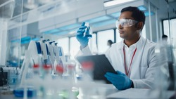 Medical Research Laboratory: Portrait of a Handsome Male Scientist Using Digital Tablet Computer, Analysing Liquid Biochemicals in a Laboratory Flask. Advanced Scientific Biotechnology Laboratory.