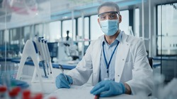 Medical Research Laboratory: Portrait of Male Scientist Wearing Face Mask Looking at Camera, Writing Down Information. Advanced Scientific Lab for Medicine, Biotechnology, Microbiology Development