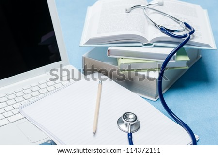 Medical research stethoscope lying on doctor book pen and paper - stock photo
