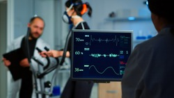 Medical researcher examining EKG image showing on monitor while patinet with mask running on cross trainer testing heart rate using electrodes.Doctor monitoring physical endurance in science sport lab