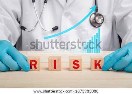 Medical safety and Risk awareness. A doctor and wooden letter blocks spelling risk. Semi transparent sets of graphs represents increasing harms associated with health care. Hospital risk concepts. Сток-фото ©