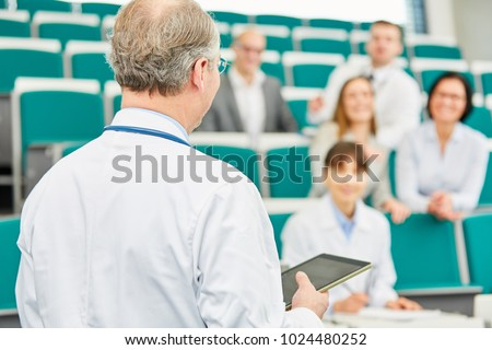 Medical school lecturer teach doctors in lecture hall with tablet
