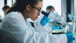 Medical Science Laboratory: Beautiful Black Scientist Looking Under Microscope Does Analysis of Test Sample. Diverse Team of Young Specialists, Using Advanced Technology Equipment.