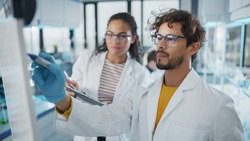 Medical Science Laboratory: Handsome Latin Male Scientist Writes Detailed Project Data Analysis on the Board, His Black Female Colleague Talks. Young Scientists Solving Problems.