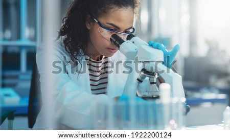 Medical Science Laboratory: Portrait of Beautiful Black Scientist Looking Under Microscope Does Analysis of Test Sample. Ambitious Young Biotechnology Specialist, working with Advanced Equipment