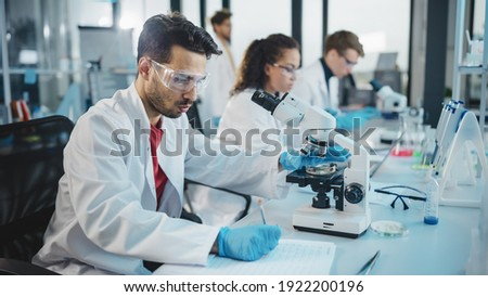Medical Science Laboratory: Portrait Shot of a Handsome Latin Scientist Looking Under Microscope, Doing Sample Analysis. Young Biotechnology Specialist, Using Advanced Equipment.