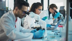 Medical Science Laboratory: Row of Diverse Team of Multi-Ethnic Young Scientists Looking Under Microscope, Analyze Chemicals, Talk, Solving Problems. Biotechnology Specialists working in Advanced Lab