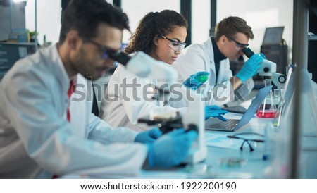 Medical Science Laboratory: Row of Diverse Team of Multi-Ethnic Young Scientists Looking Under Microscope, Analyze Chemicals, Talk, Solving Problems. Biotechnology Specialists working in Advanced Lab Foto stock ©