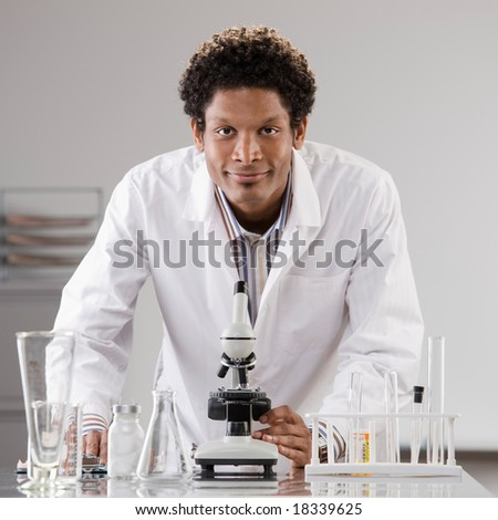 Medical scientist wearing lab coat posing with microscope and test tubes in laboratory