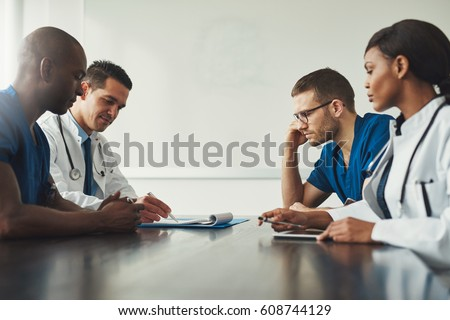 Medical staff meeting. Group of young people in white coats and blue uniform sitting at table in front of each other. Low angle side view with copy space #608744129