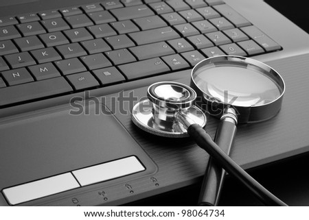 Medical stethoscope and magnifying glass on laptop keyboard. In B/W