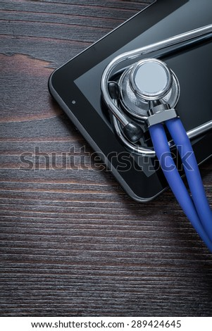 Medical stethoscope and touch-sensitive pad on vintage wooden background medicine concept