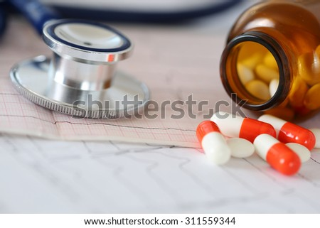 Medical stethoscope head lying on cardiogram chart with pile of pills closeup. Cardiology care, health, protection, prevention and help. Healthy life or insurance concept