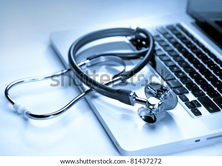 Medical stethoscope on a laptop computer in blues, closeup