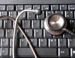 Medical stethoscope on top of laptop computer keyboard. Illustrative of healthcare and technology, informatics, bioinformatics and computers in clinics, hospitals, digital health related environment.