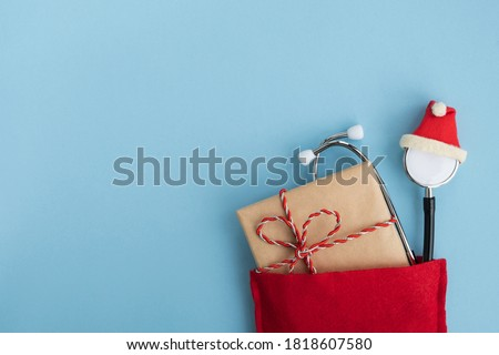 Medical stethoscope wearing hat with gift box in Santa Claus red bag. Christmas and New Year concept. Creative medical winter greeting card. Top view, flat lay, copy space