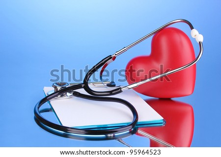 Medical stethoscope with clipboard and heart on blue background