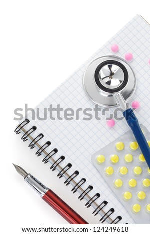 medical stethoscope with pills and notebook isolated on white background