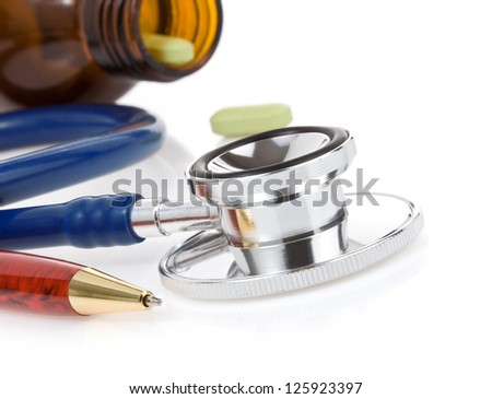 medical stethoscope with pills isolated on white background