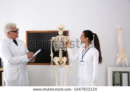 Medical student and professor studying human skeleton anatomy in classroom