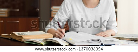Medical student preparing for classes in university. Woman makes notes at her workplace. Education concept. Foto stock ©