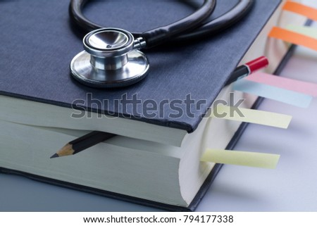 Medical student textbook with pencil and multicolor bookmarks and stethoscope isolated on white